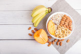 A plate with muesli, almonds, banana, persimmon on a white wooden background with copy space.