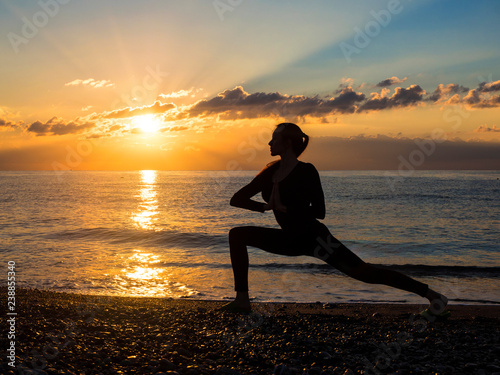 Foto Murales Young healthy woman practicing yoga fitness exercise on the beach at sunset. Healthy lifestyle concept. Copy space text