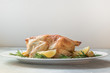 Leinwanddruck Bild - Roasted chicken with potatoes and rosemary on white table. Copy space.