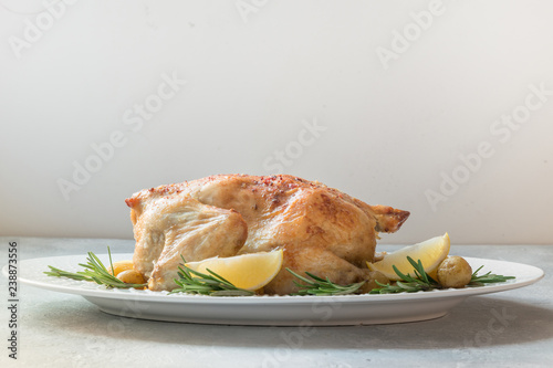 Leinwanddruck Bild Roasted chicken with potatoes and rosemary on white table. Copy space.