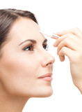 Smiling woman applying concealer on face, isolated - 238885144