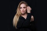 Sexy lady diva with long blonde hair in long coat posing in studio, dark background. Elegant woman. Erotic noir concept. Half body.