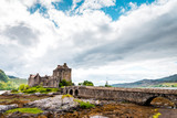 Eilean Donan Castle in the Highlands of Scotland on a cloudy day and low tide, ancient castle with sandstone bridge, lush nature with colorful moss and lichens