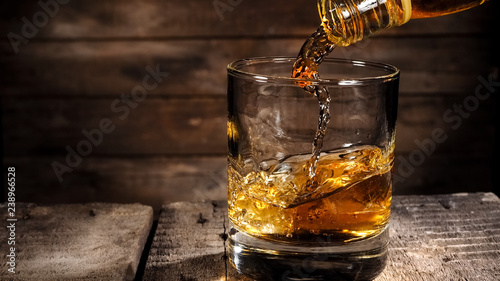 Whiskey pouring in a glass on wood background