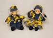 Leinwanddruck Bild - Zwei kleine Puppen mit gelb blauer Kleidung