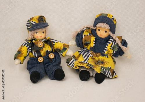 Leinwanddruck Bild Zwei kleine Puppen mit gelb blauer Kleidung