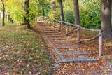 steinerne Treppe mit Holzgeländer in einem herbstlichen Park in Stege