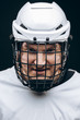 Portrait of hockey keeper in protective helmet with carbonic defence in white uniform grinning at camera over black background