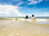 Children on the beach and wide view of sea with blue sky