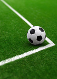 Soccer ball on green football field