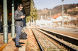 Young traveler man holding smartphone while waiting for train