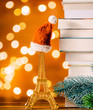 Christmas Santa Claus hat on Eiffel tower toy and pile of books with fairy lights on background