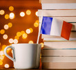 White cup with France flag near books on fairy lights background