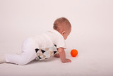 little baby playing with orange ball in white studio