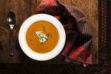 Overhead shot of a bowl of pumpkin soup on an old wooden table