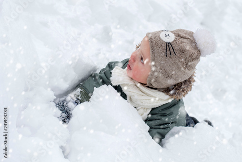 Little boy in warm clothes enjoying first snow and having fun outdoor