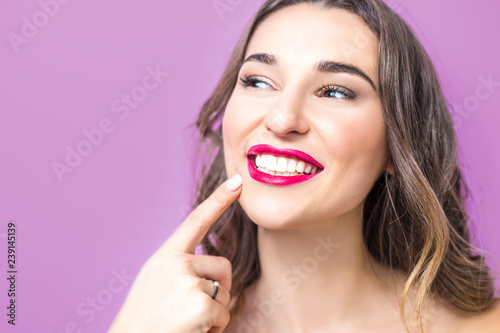 Dentistry concept. Beautiful young woman smiling, showing healthy white teeth, red lipstick. Close-up of a girl on a pink background.