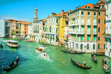 Venice, Italy, August 14, 2018: gondolas, river taxi and boats on the Grand Canal in Venice, old historic buildings background