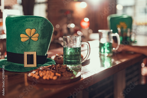 Leprechaun hat, mug of green beer and snacks on bar counter