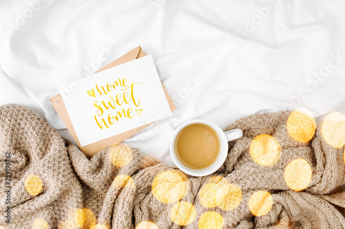 Mockup card and Cup of coffee on bed with warm plaid. Copy space. Flat lay, top view - 239198762