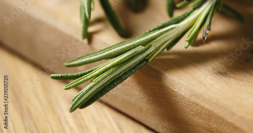 Closeup   of fresh rosemary bunch on wood table