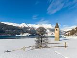 Sunken Church Tower in frozen lake near Graun on Resia Lake, South Tyrol