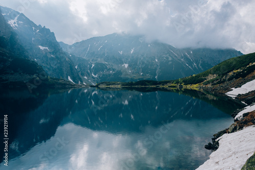 Reflection of mountains in sky water of Czarny Staw pond, Tatra Mountains, Poland