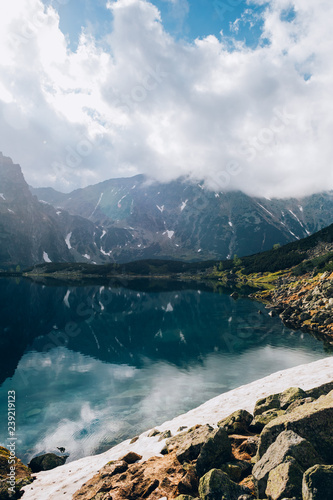 Reflection of mountains and sky in water of Czarny Staw pond, Tatra Mountains, Poland