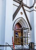 Man Staining Church Door