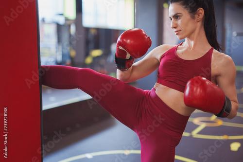 Modern adult sportswoman boxing in gym