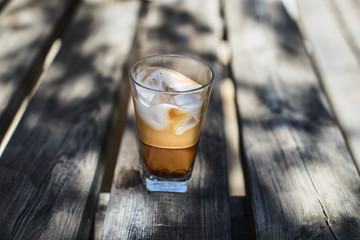 Iced coffee with milk and ice cubes on a wooden table