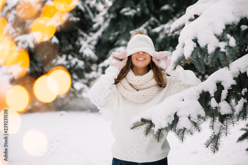 Outdoor close up portrait of young beautiful happy smiling girl wearing white knitted, scarf and gloves. The model jokes and closes the eyes with hat in park with Christmas lights.