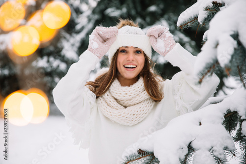 obraz PCV Outdoor close up portrait of young beautiful happy smiling girl wearing white knitted beanie hat, scarf and gloves. Model posing in park with Christmas lights. Winter holidays concept.