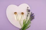 Lavender essential oil set in glass bottles and lavender flowers on pink heart on pastel lilac background.Organic Natural  Oil
