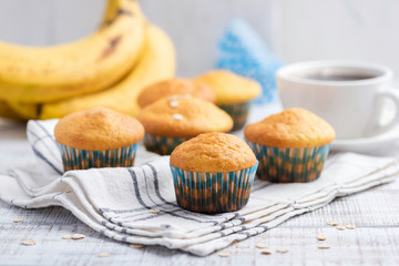 Healthy banana muffins with oat flakes on white table