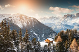 Wooden house in the winter mountains at sunset. Dolomite Alps, Val di Fassa, Italy