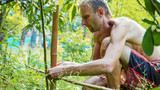 A caucasian man using bamboo wood for building natural fence in the garden © alexeg84