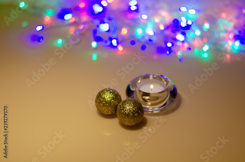 Christmas golden balls and a burning candle in a crystal candlestick on a mirrored table against the blurry lights of the Christmas garland - 239279370