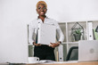 african american businesswoman holding folders in modern office