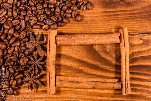 Frame of cinnamon sticks, coffee beans and star anise on wooden table