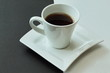 White and black. White porcelain cup with fragrant hot coffee on figured exclusive porcelain saucer. Contrast background.