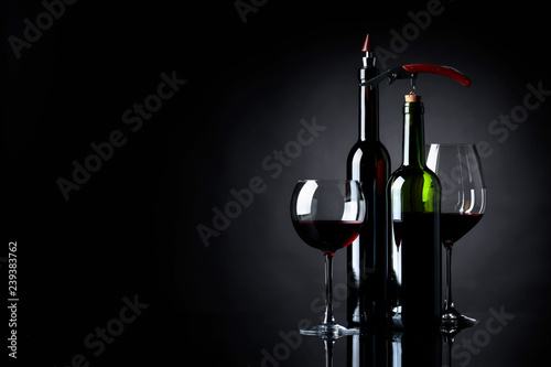 Red wine with corkscrew on a black background. - 239383762