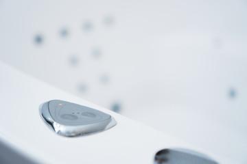 Hydromassage bathtub control buttons in bathroom.