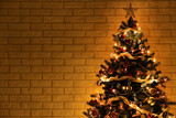 Christmas tree with decorations on brick wall background