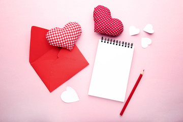 Fabric hearts with envelope, notebook and pencil on pink background © 5second