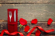 Fork and knife with red rose on wooden table