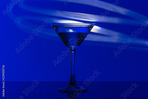 Martini glass on blue background and bright club lights. - 239430736