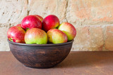 Fresh apples on a metal plate on a brick wall background. Closeup, selective focus