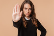 Image of displeased woman 20s showing stop gesture with hand, isolated over beige background