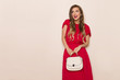 Smiling Beautiful Woman In Red Dress With Beige Purse Is Looking Away And Talking